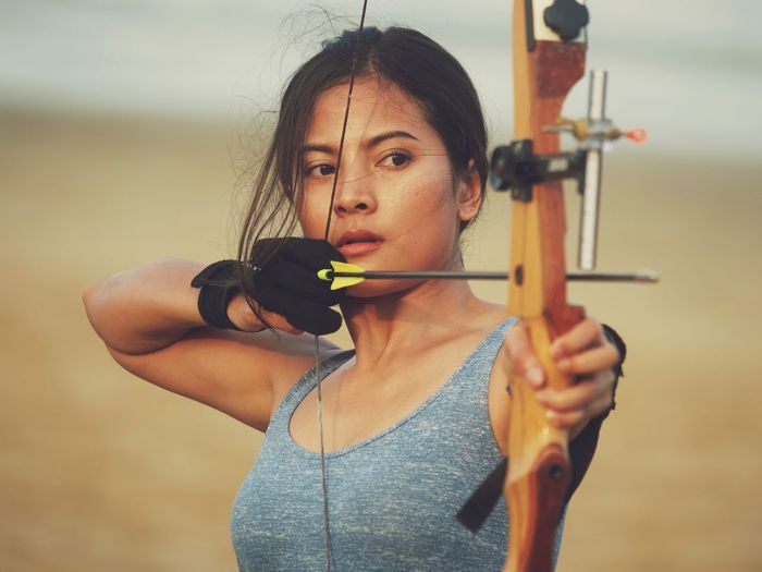 Archery One Person Holding Young Adult Front View Young Women Strength Sport Arrow - Bow And Arrow Aiming Women Portrait Concentration Standing Archery Indoors  Adult Lifestyles Practicing Weapon