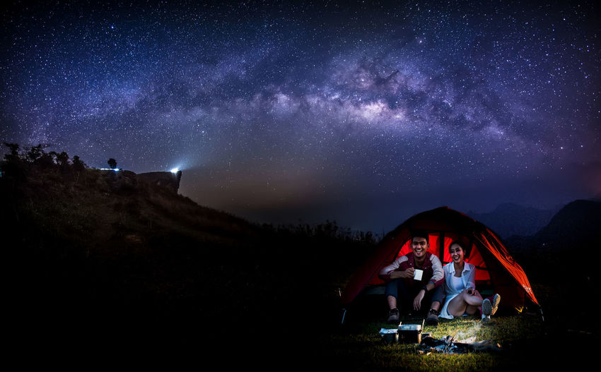 Male and female tourists are in tents on the top of the hill amid the Milky Way galaxy in the sky. Long exposure photograph, with grain.Image contain certain grain or noise and soft focus. Camping Adult Mountain Infinity Real People Star Field Beauty In Nature People Illuminated Scenics - Nature Milky Way Star Nature Astronomy Galaxy Sky Space Night Star - Space Men