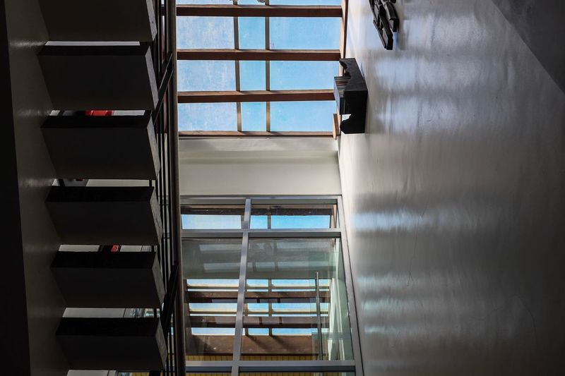 House Indoors Perspective Looking Up Blue Sky Sun Roof Sunroof Modern House Upstairs Stairs Indoors  Architecture No People Window Security Built Structure Metal Glass - Material Wall - Building Feature Sunlight Building Closed Railing Protection