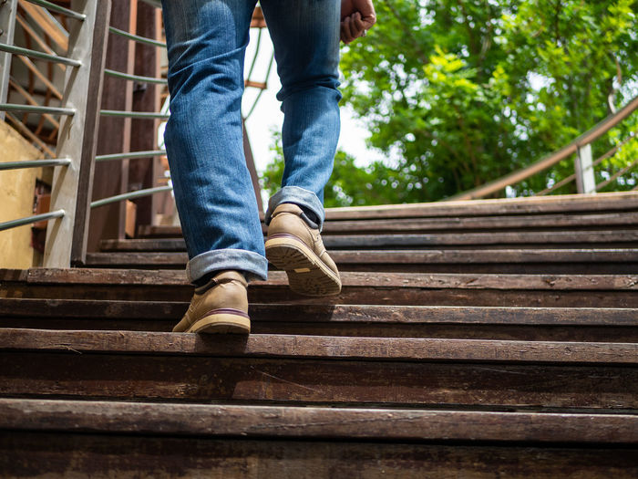 Adult man walking up the wooden stairs. Moving forward Concept. Staircase Human Leg Low Section Architecture Human Body Part One Person Jeans Body Part Men Casual Clothing Shoe Moving Up Steps And Staircases Low Angle View Day Railing Leisure Activity Real People Outdoors Human Limb Human Foot