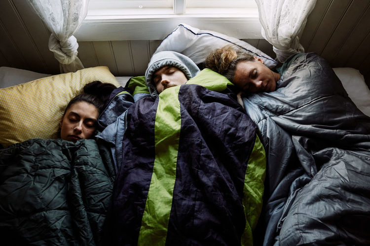 High angle view of people sleeping on bed