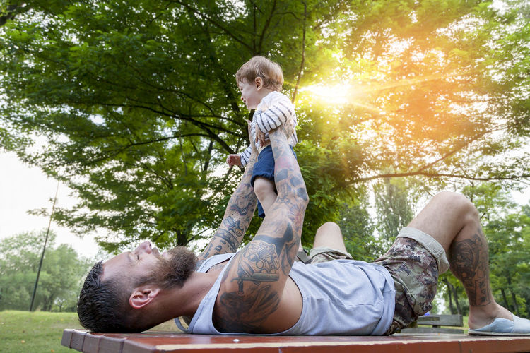 Father carrying son while lying on table against trees