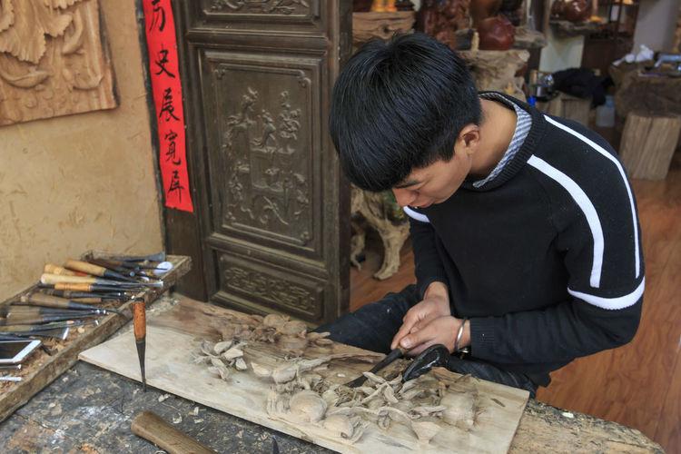 Shaxi, China - February 21, 2019: Chinese artist carving a wood plate in Shaxi old town Shaxi Yunnan Yunnan ,China Kunming, China Market Horse Horses South Silk Road