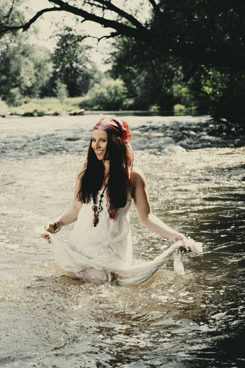 Young women crossing a river One Person Young Adult Real People Young Women Leisure Activity Lifestyles Women Front View Long Hair Beautiful Woman Beauty Hairstyle Nature Adult Portrait Fashion Hair Water Full Length Outdoors Boho River Summer Hippie Freedom