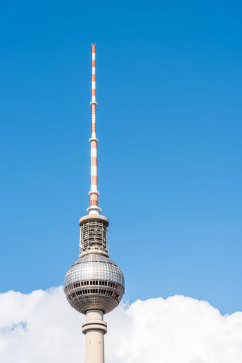 Television tower against blue sky with clouds