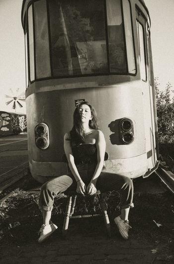 Portrait of a girl sitting on car