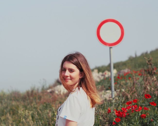 Portrait of smiling young woman standing by plants against sky