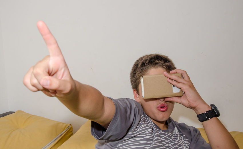 Close-up of boy watching in smart phone through cardboard virtual reality simulator
