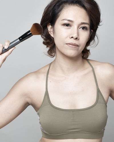 Woman Applying Make-Up With Brush Against Gray Background