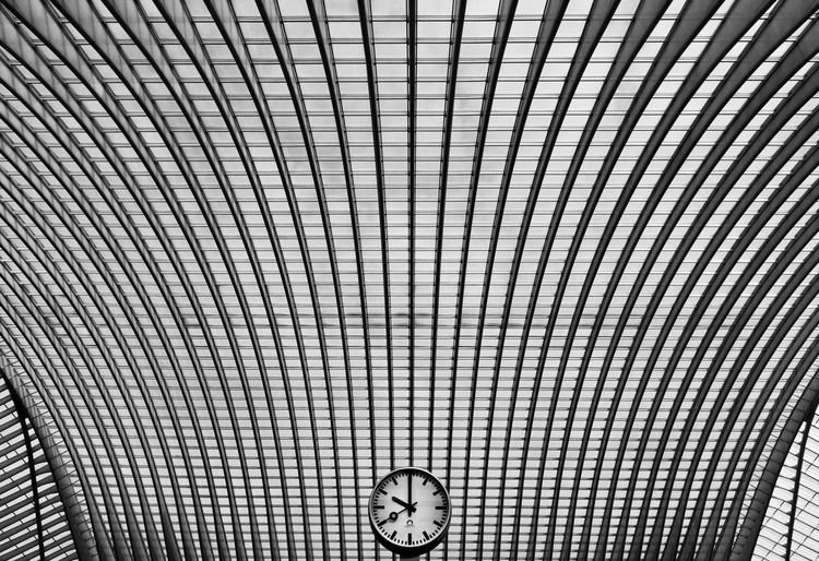 Low angle view of clock against patterned ceiling