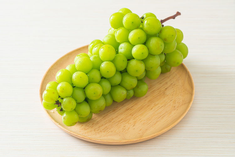 High angle view of grapes in container on table