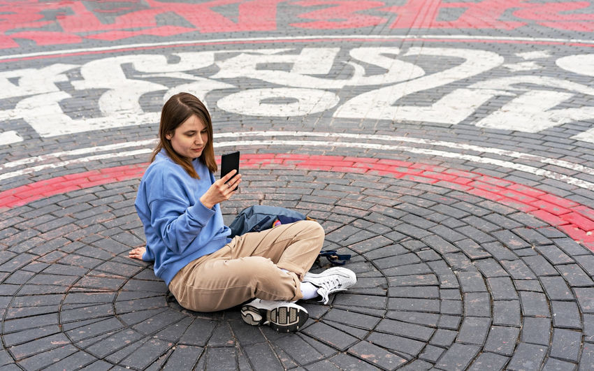 Full length of man using mobile phone while sitting on street