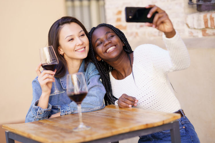 Cheerful friends doing selfie while sitting at cafe