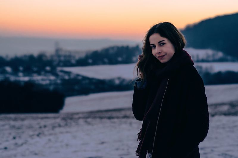 The City in the background Portrait Focus On Foreground Looking At Camera Sunset Young Women Sky Outdoors City Blurry Sun Winter Wintertime One Person Standing Front View Smiling Happiness Winter Portrait Scarf Cold Temperature Warm Clothing Brown Hair Sunlight Hair Jena