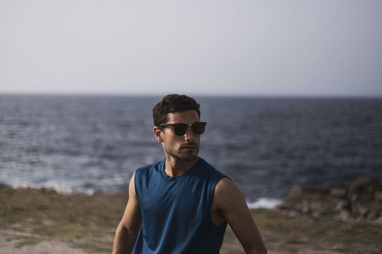 Young man in sunglasses against sea