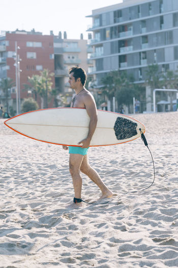 Full length of shirtless man carrying surfboard on beach