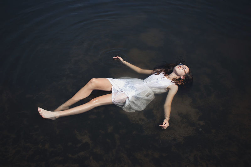 High angle view of woman relaxing in sea