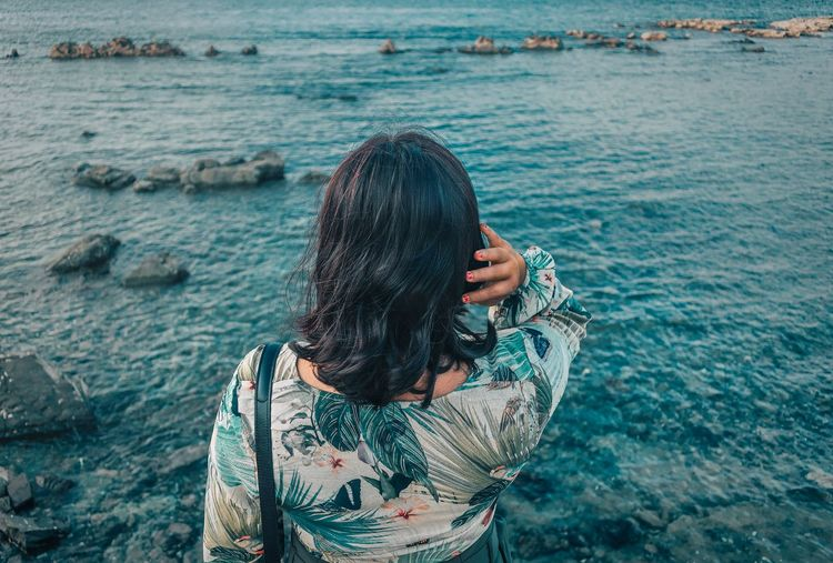 Rear view of woman standing in sea