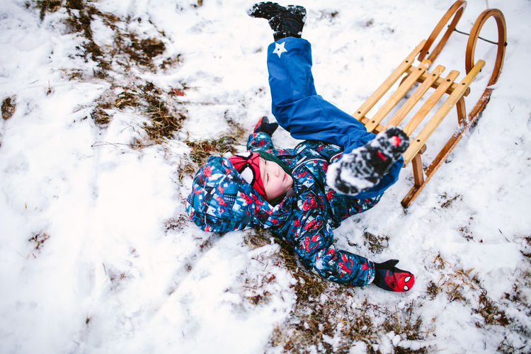High angle view of child on snow covered land