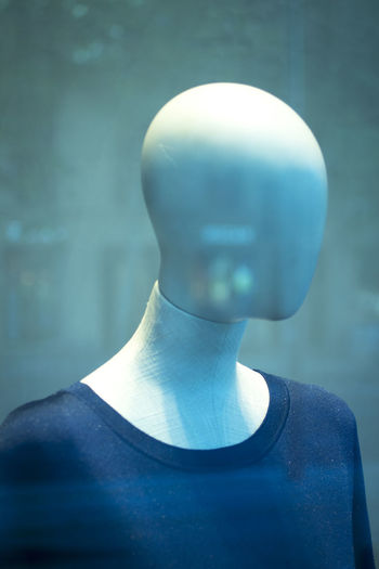 Close-up of mannequin in store seen through glass window