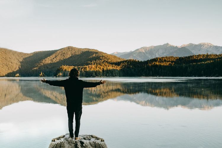 Man is standing with arms wide open at the lake Person In Nature Man Arms Outstretched Arms Wide Open Silhouette Lake Lake View Lakeshore Eibsee Freedom Travel Bavaria Early In The Morning Early Morning Reflections In The Water Mirror Reflection Mountains Beauty In Nature Nature Young Adult Black Germany Berchtesgaden Rock Shore People Standing At Lake