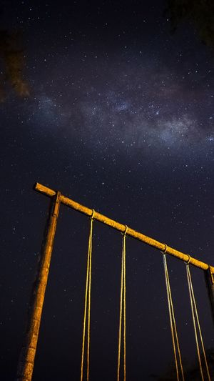 Low angle view of swing against sky at night