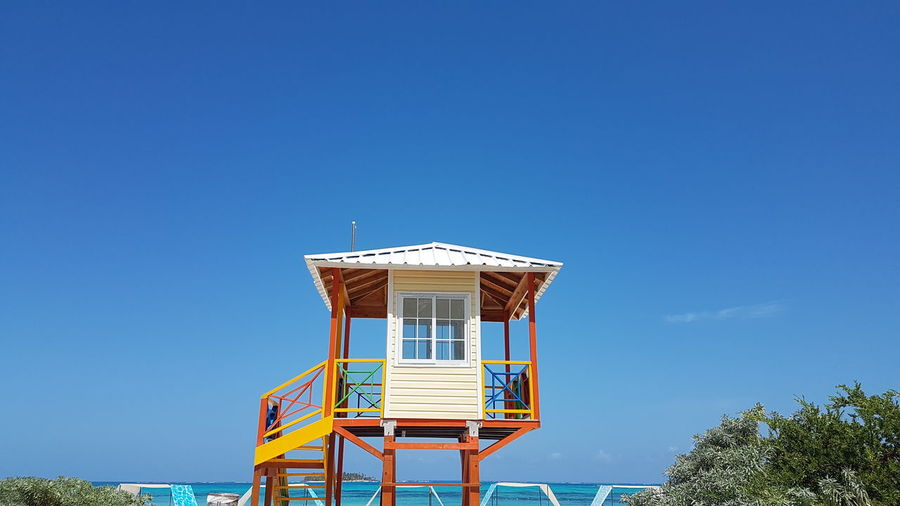 Low angle view of hut on beach against clear blue sky