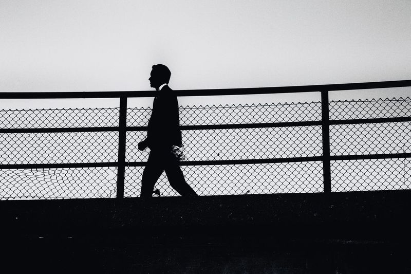 Rear view of silhouette man walking against clear sky