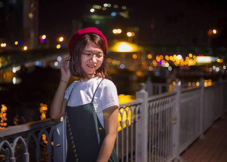 Thoughtful young woman smiling while standing against canal in illuminated city at night