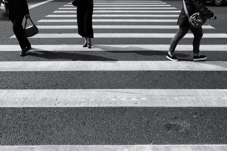 Low section of women on zebra crossing in city