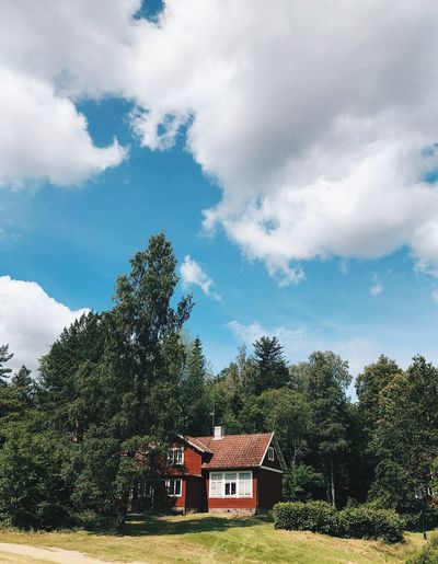 House amidst trees and buildings against sky