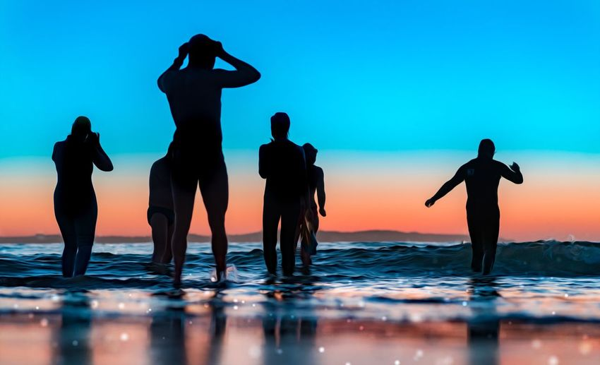 Silhouette people standing by swimming pool against sky during sunset