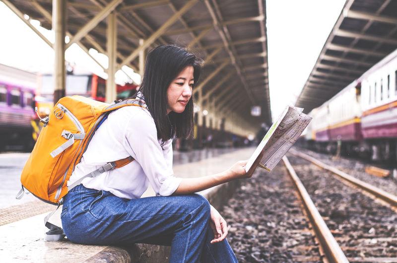 Woman Reading Map At Railroad Station Platform