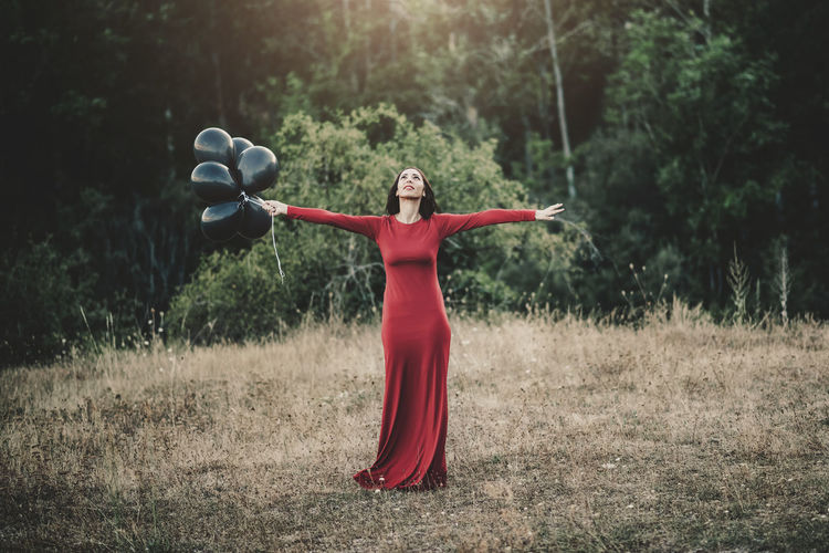 Woman in red dress with arms outstretched holding balloon while standing on field