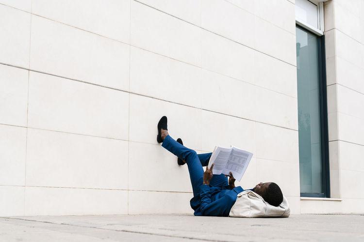 Man lying down against wall