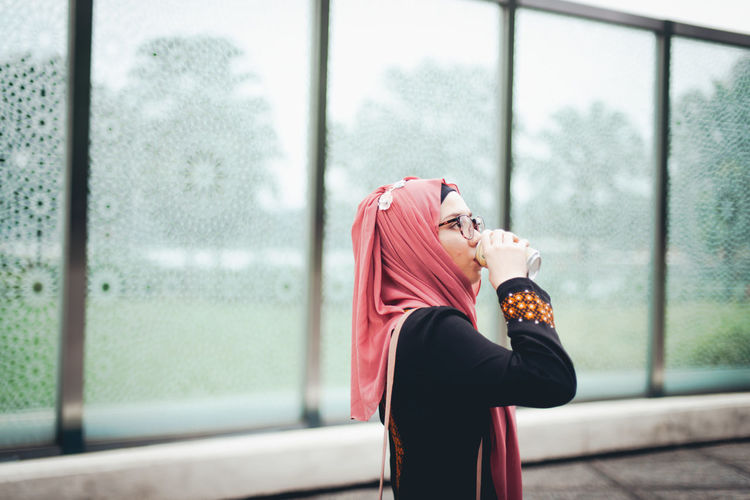 One Person Real People Side View Lifestyles Focus On Foreground Women Standing Young Women Young Adult Leisure Activity Adult Hijab Clothing Headscarf Day Window Three Quarter Length Profile View Outdoors Contemplation Beautiful Woman