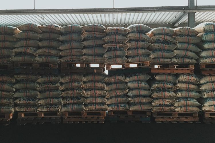 Stack of coffee beans in burlap sacks at warehouse