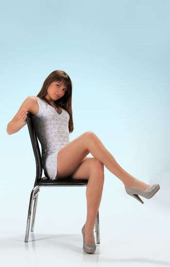 Full length portrait of sensuous young woman sitting on chair against blue background
