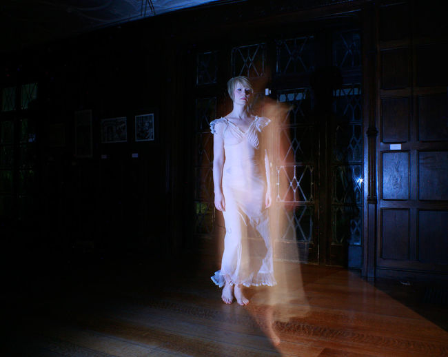 Blurred motion of woman walking in house