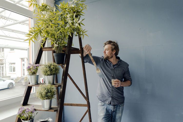 Young man looking at potted plant