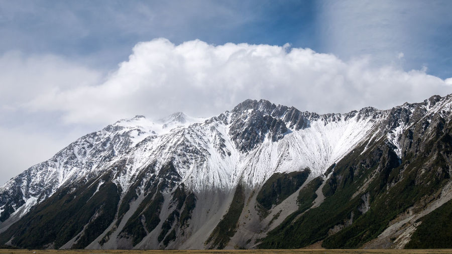 Mountain range with puffy clouds above partially lit by sun. aoraki mt cook national p, new zealand