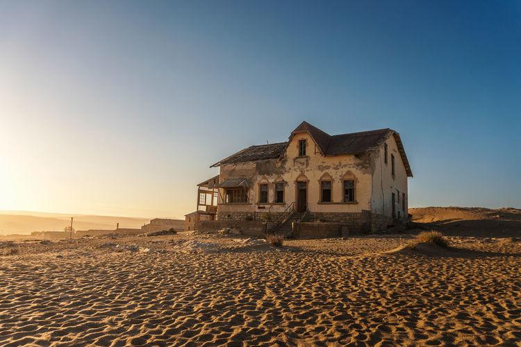 House on beach against clear sky