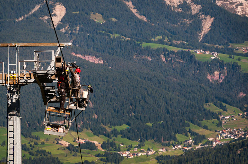 Hazardous work, maintenance of a cable car during the summer Hazardous Safety First! Working Mountain Oil Pump Overhead Cable Car Safety Equipment Scenics Ski Lift Transportation