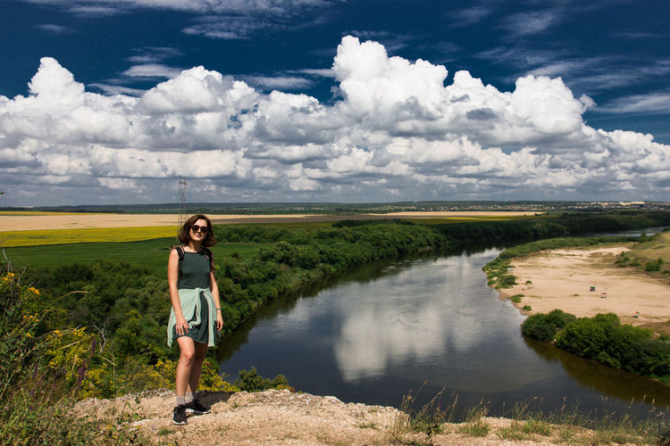 Portrait of woman standing at riverbank against cloudy sky
