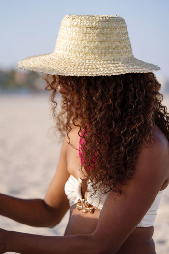 Young woman with curly hair choosing a necklace to wear at the beach