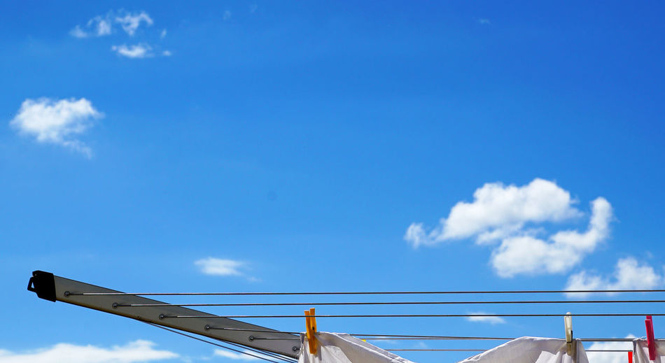 Fabric Attached To Clothespins On Clotheslines Against Blue Sky