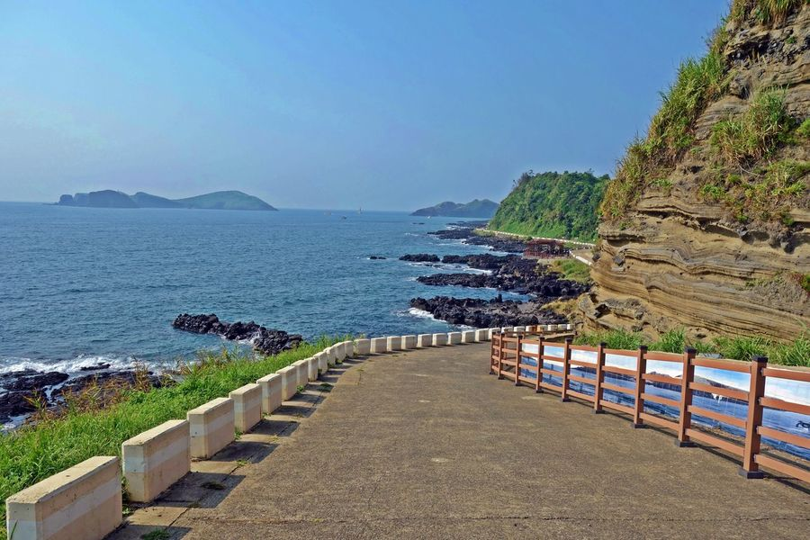 a Eongal coastal walking trail view between a sea and outcrops of volcanic deposits,jeju island,korea,asia ASIA Basaltic Beach Blue Coast Deposits Eongal Island Jeju Korea Mountain Nature Outcrops Rocks Sea Sky Trail Tranquility Travel Trip View Volcanic  Walking Water Waves