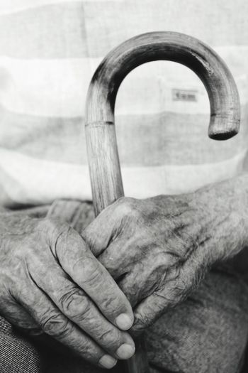 Midsection Of Senior Man Holding Walking Cane