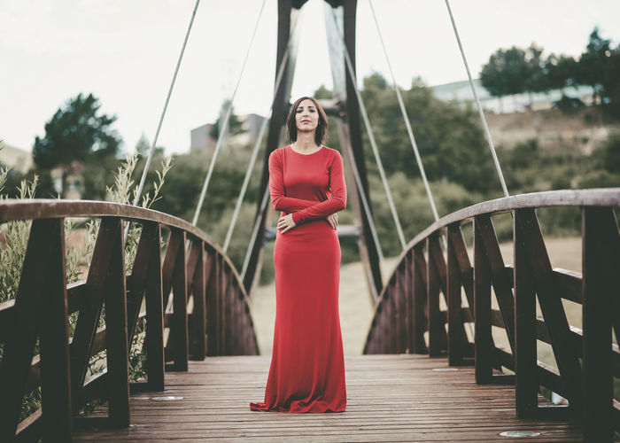 Portrait of young woman standing on footbridge