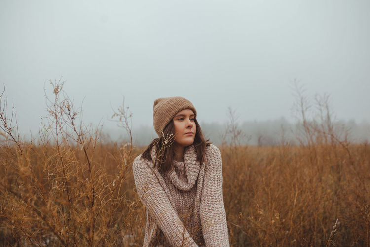 Portrait of beautiful young woman standing in a fog against sky during late autumn winter